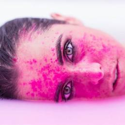 Girl with blue eyes and wet hair inside a bath of milk with pink powder on face